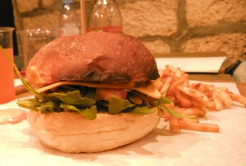 Une photo terne, de qualité médiocre, clairement prise par un autre appareil photo. Elle montre un burger qui n'a pas de sésame sur le dessus.