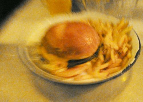 burger et frites dans une assiette creuse, mais très flou (ce qui donne un effet de vitesse)