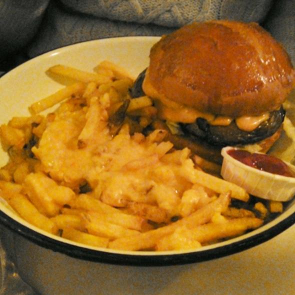 Le burger vg, servi dans une assiette creuse avec des frites et du ketchup