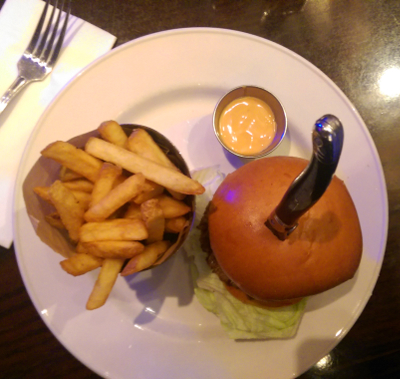 Vue de haut : le burger, un couteau planté dedans, les frites et la sauce
