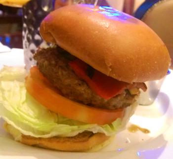 Vue de près : le bun, beaucoup de salade, une grosse tranche de tomate, le steak, et du poivron