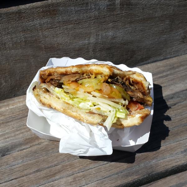 Burger entamé : on voit le contenu du burger. Beaucoup de salade, des champignons, une tomate.