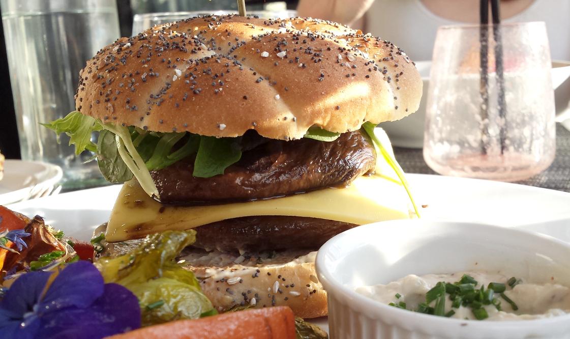 Le burger vegan vue de pres. Les champignons géants enserrent le formage